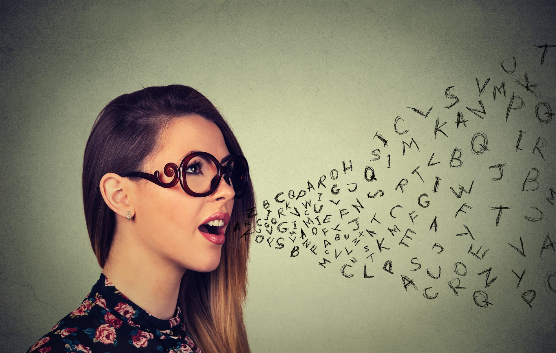 Woman in glasses choosing her words with alphabet letters coming out of her mouth. Communication, information, intelligence concept.
