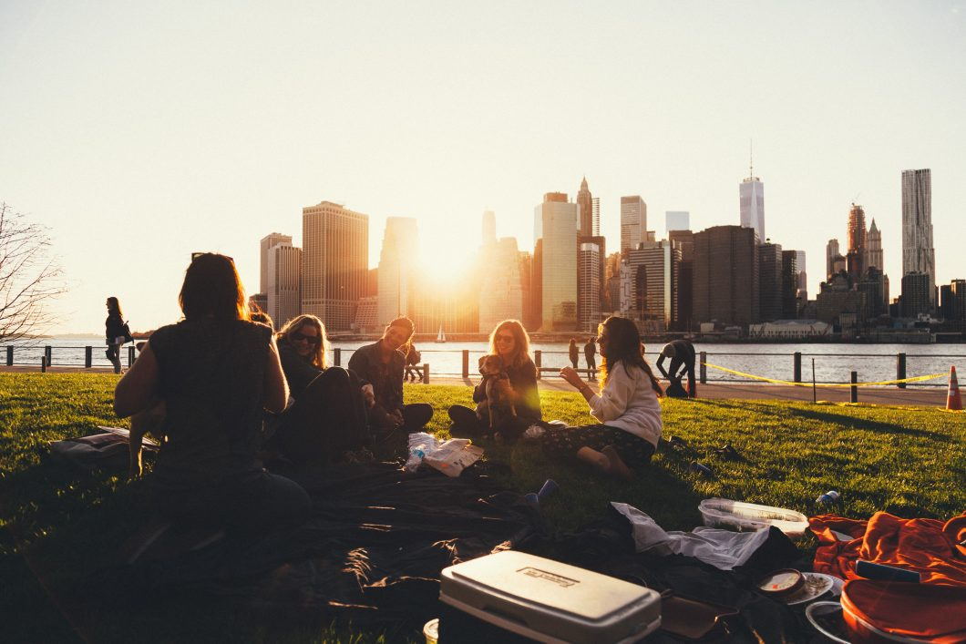 A group of friends sitting on the grass outside of a city, enjoying their friendships.