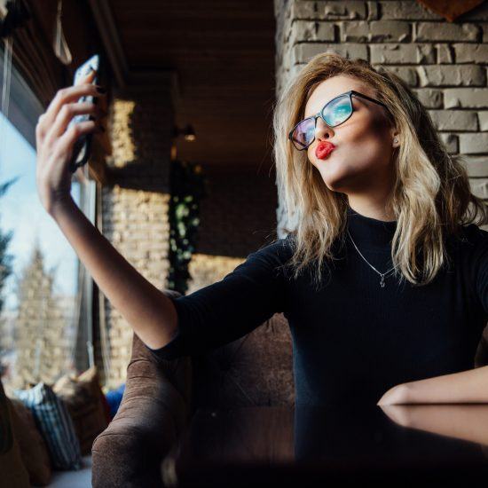A young beautiful, narcissistic blonde woman taking a selfie in coffee shop.