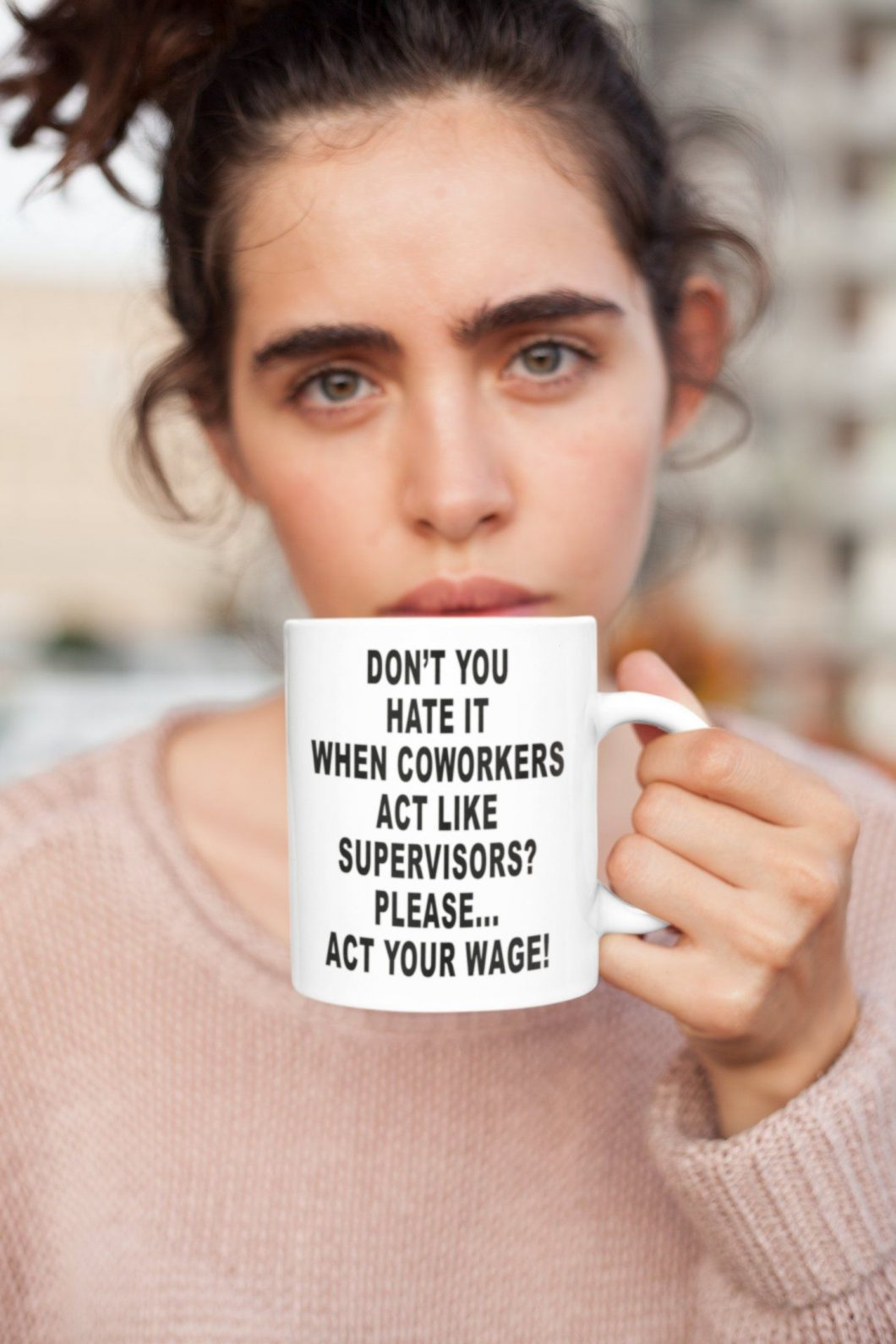 A pretty woman at work holding a white cup of coffee with a sarcastic message written about a coworker on the cup