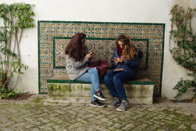 Two Iranian girls looking at their smartphones
