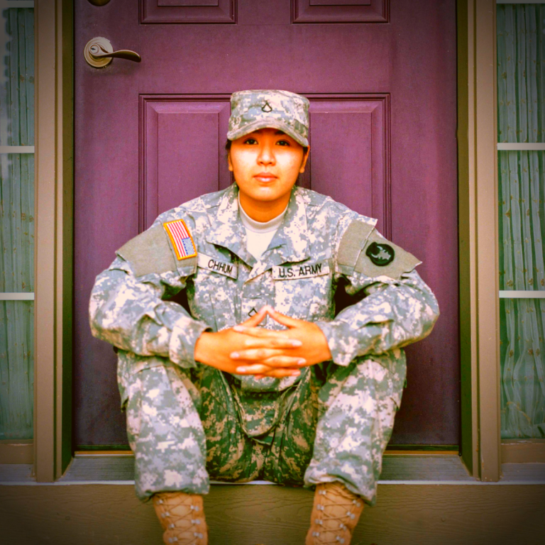 Military woman sitting on her front porch while holding her two hands together