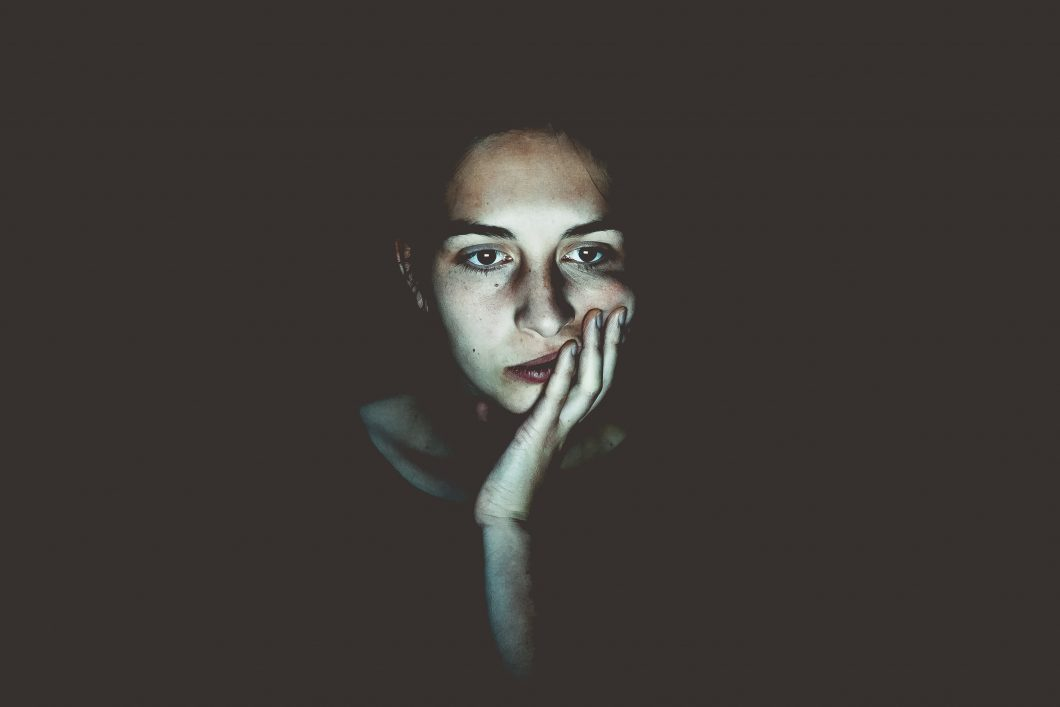 A young woman in the dark, looking very worried