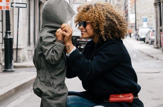 Multi-racial single mom kneeling eye-level to look at her daughter