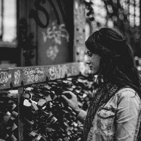 A pretty, pensive woman in front of a fence with hearts and locks contemplating her compassion for others.