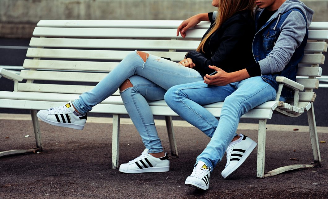 A young couple wearing jeans and Adidas shoes sitting on a park bench