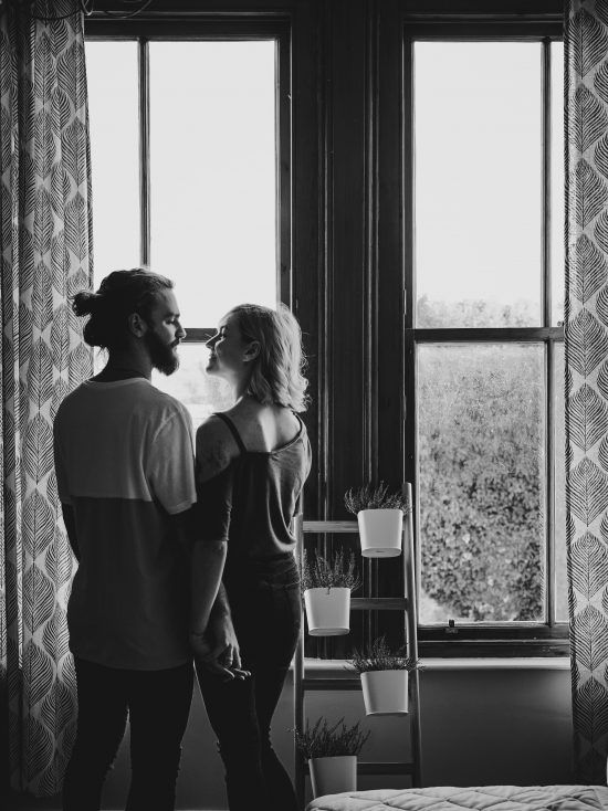 A couple in a relationship looking at each other in front of a window