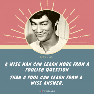 """A smiling Bruce Lee picture quote that says: """"A wise man can learn more from a foolish question than a fool can learn from a wise answer."""""""