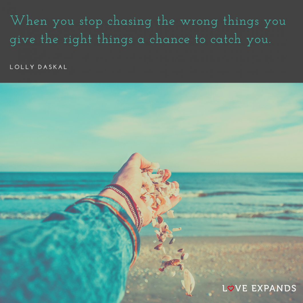 """The left hand of a woman releasing shells on the beach. Picture quote by Lolly Daskal that says, """"When you stop chasing the wrong things you give the right things a chance to catch you."""""""