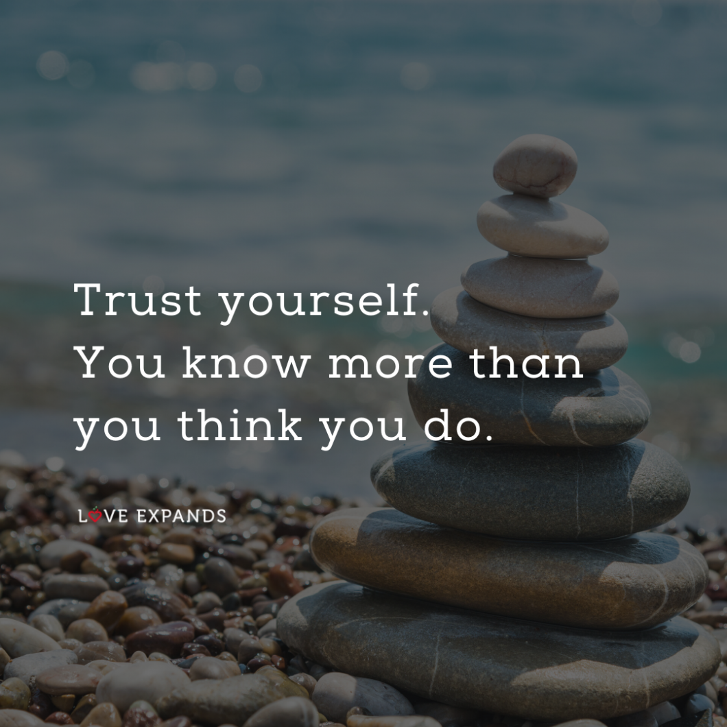 Trust yourself picture quote with rocks stacked on the beach