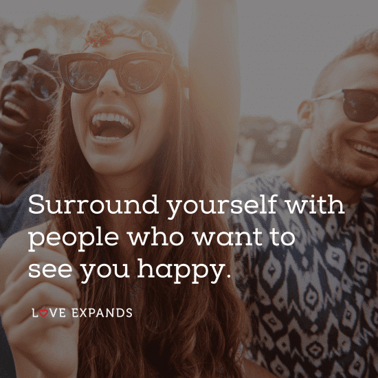 A laughing girl with sunglasses surrounding herself with people who make her happy.