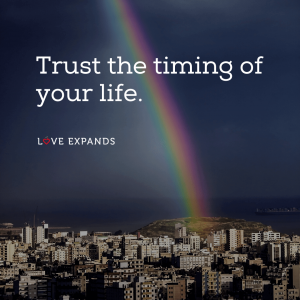"""Inspirational picture quote of a rainbow over a city: """"Trust the timing of your life."""""""