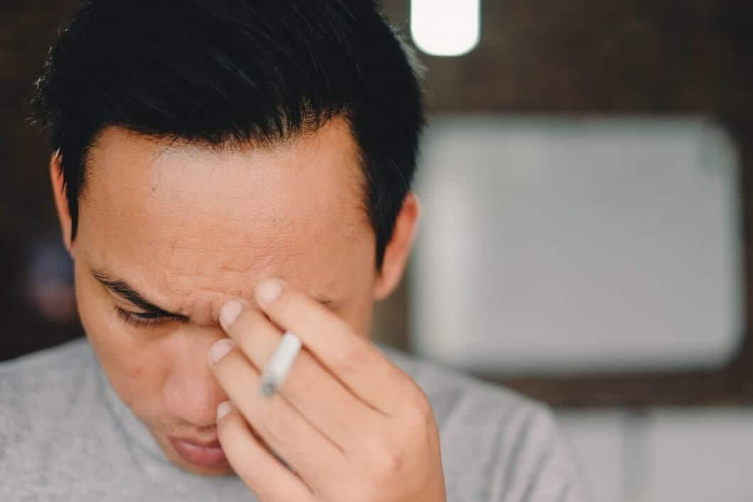 A stressed Asian man smoking a cigarette appears unable to calm his stress naurally