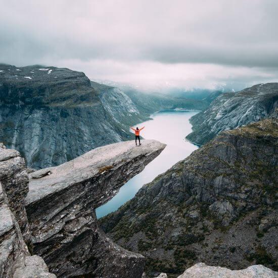 A triumphant man on a mountain ridge celebrating a fresh start