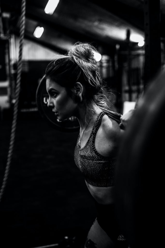 A woman in a sports bra naturally reducing stress and anxiety by exercising and lifting weights