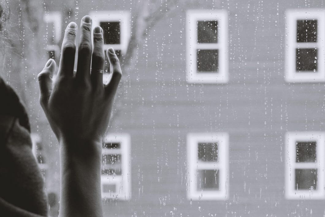 The hand of a grieving woman seeking help on a window