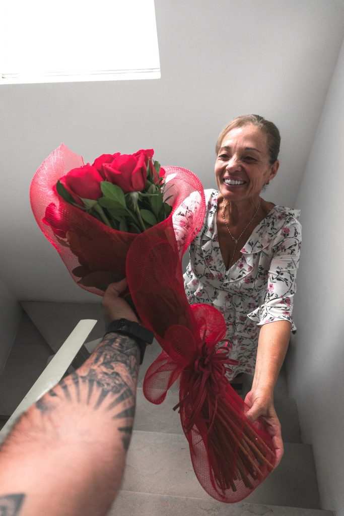 A man exercising an act of kindness and gratitude by giving an elderly lady a bouquet of roses