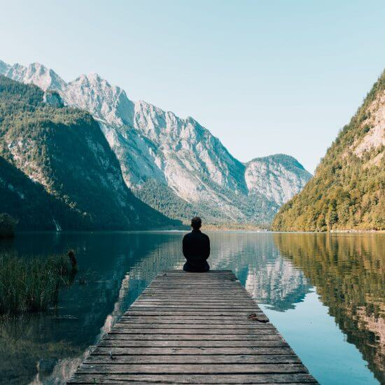 A person sitting on a deck, practicing gratitude while overlooking a body of serene water and mountains