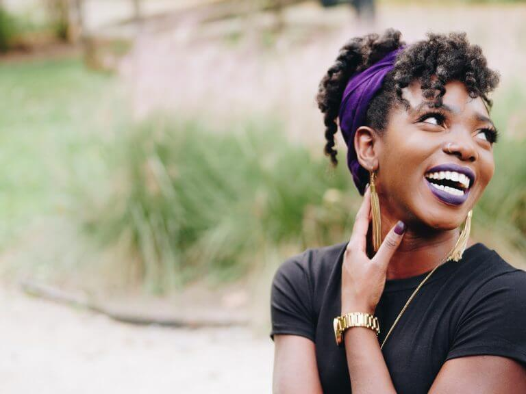 An authentic black woman wearing purple lipstick and smiling