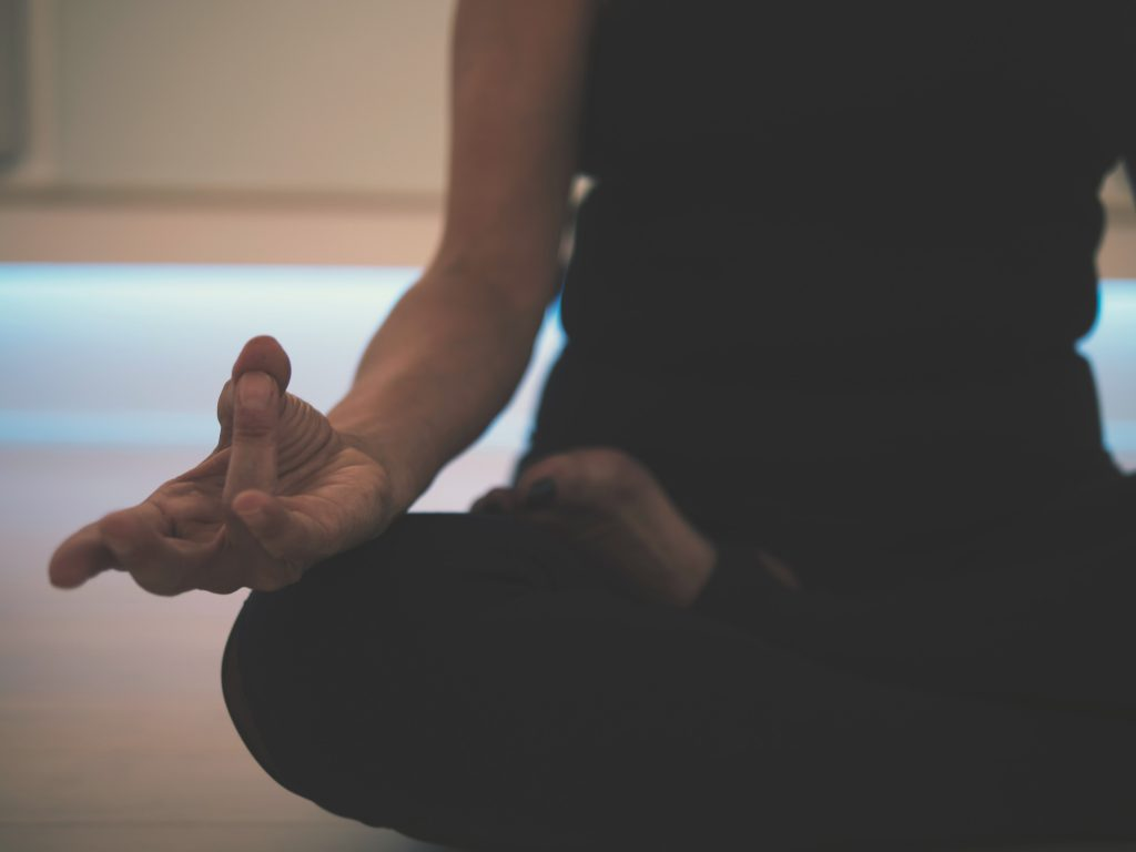 A woman meditating as a means to get over a breakup