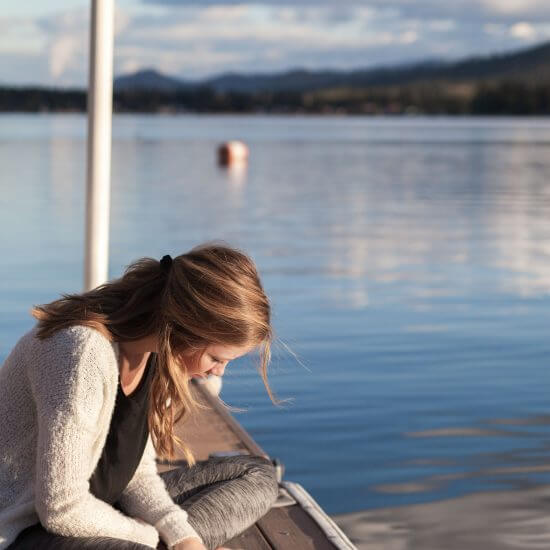 A happy and content woman reading a book by the water.