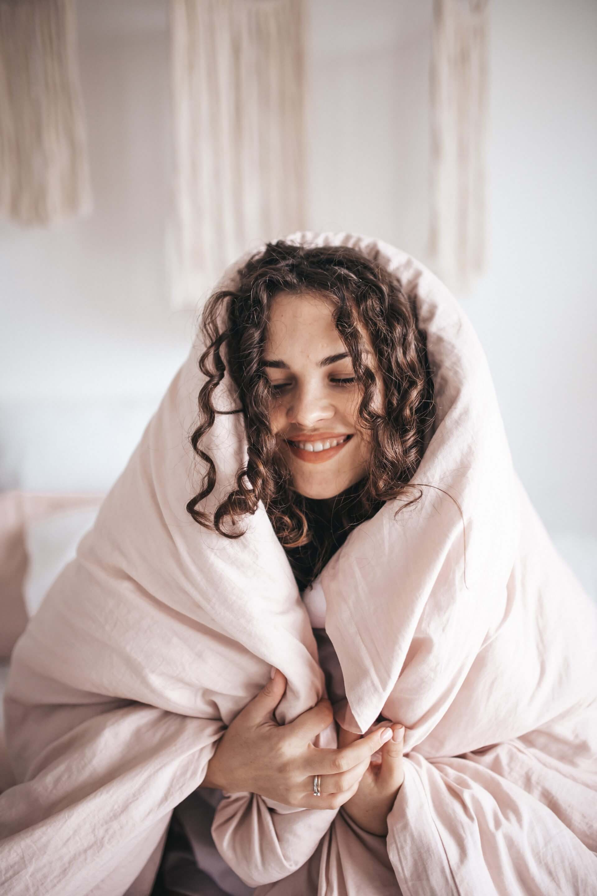 A smiling woman with a blanker wrapped around her practicing self-care.