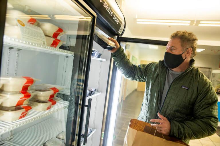 Mark Bucher, owner of Medium Rare, fills a community fridge at Takoma Park Aquatic Center.