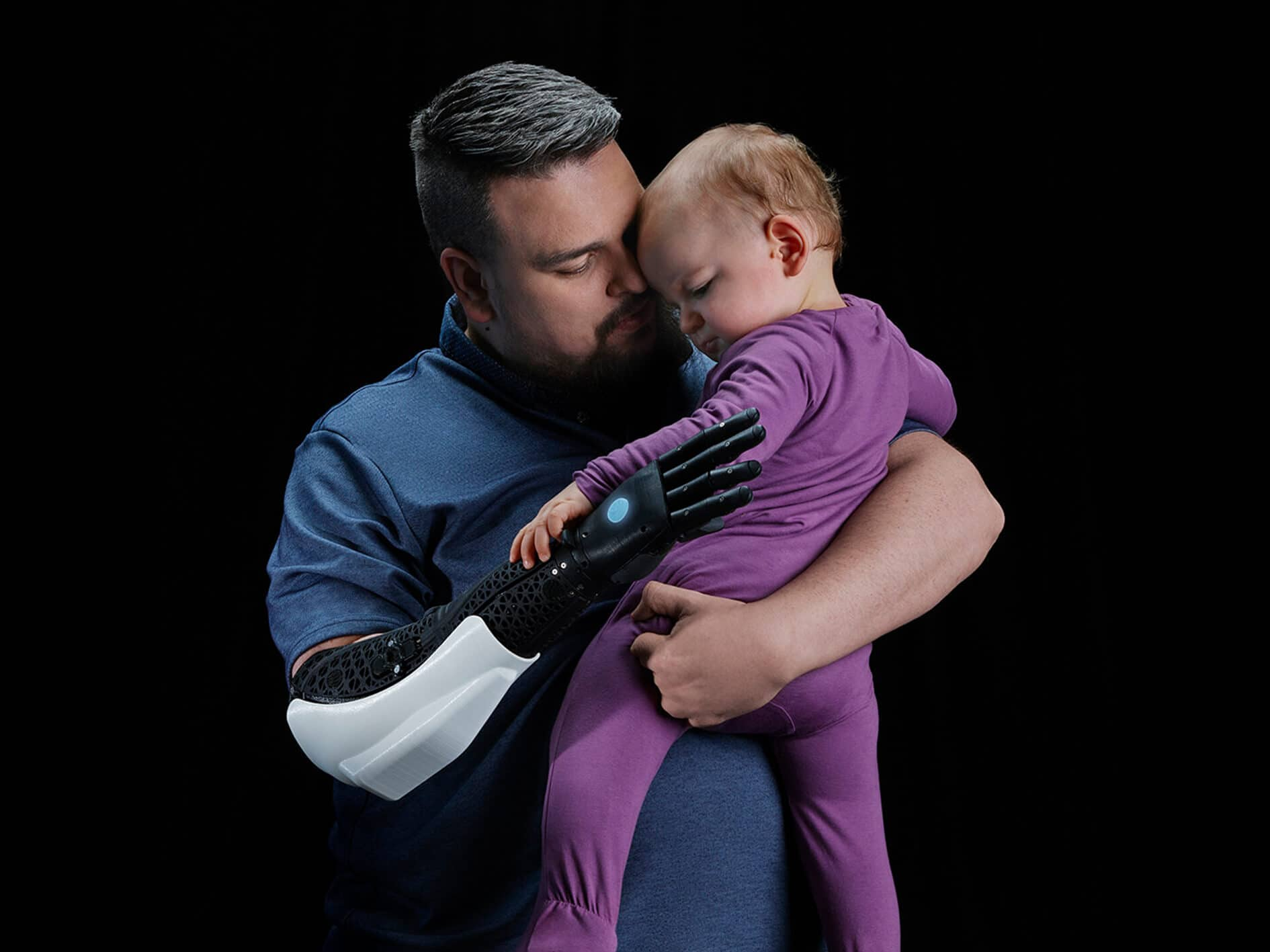 Open Bionics Empowers Amputee holding his baby with The Hero Arm Prosthetic