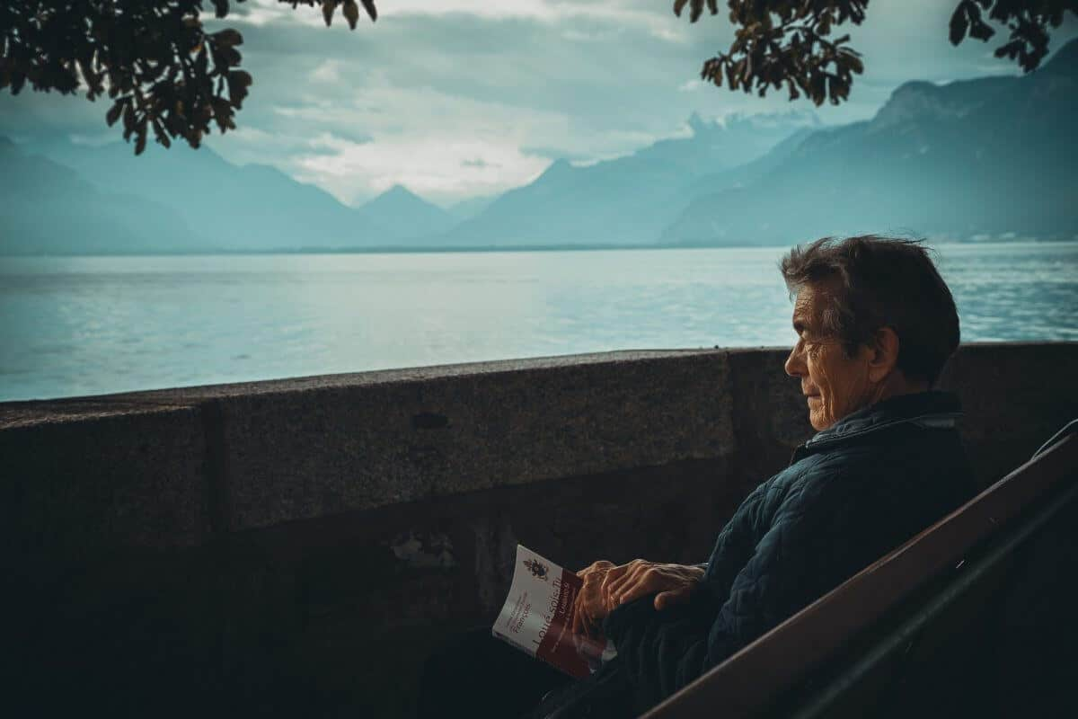 A middle-aged man with a book in hand thinking about his past while overlooking a body of water.