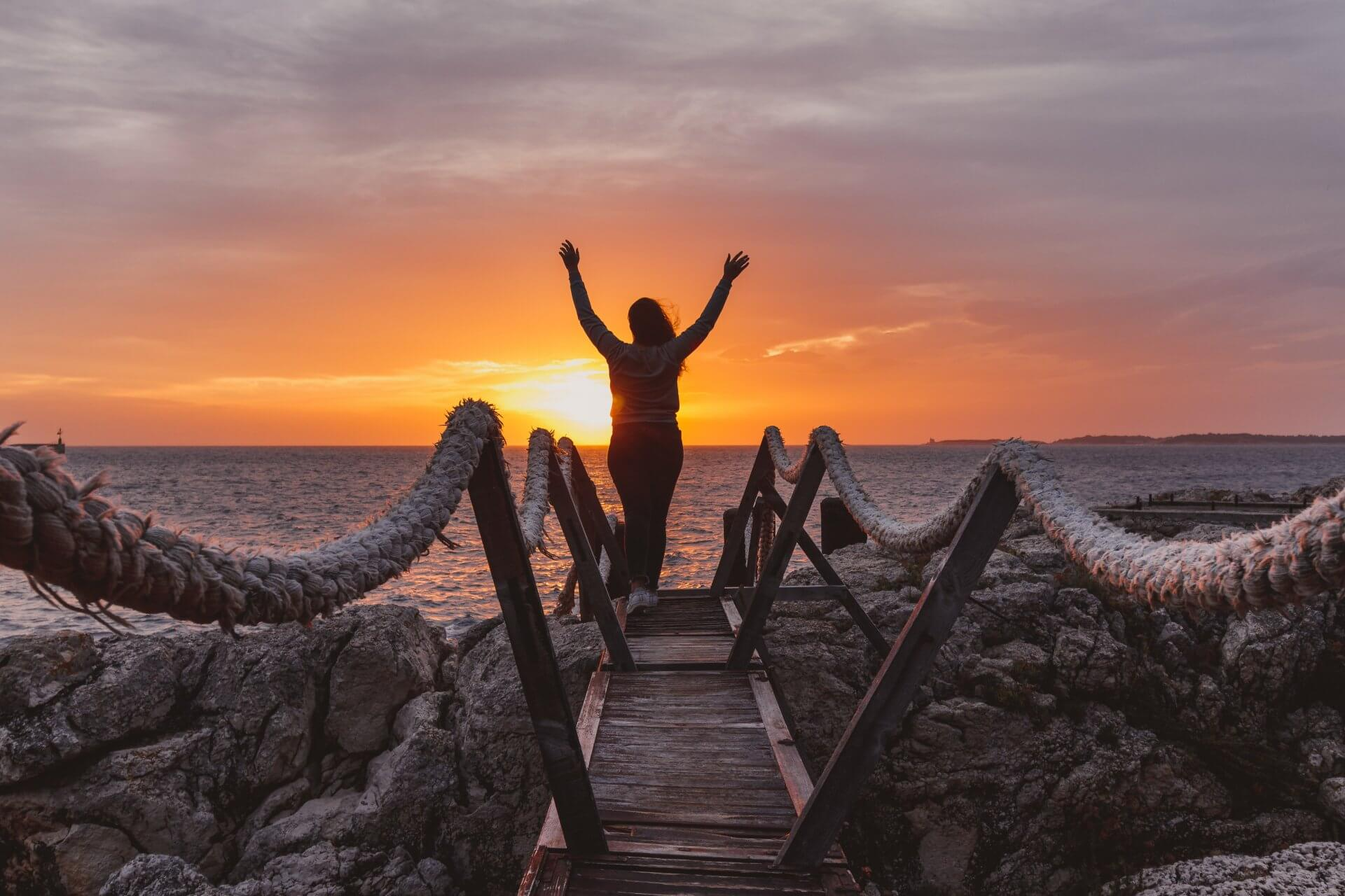 A joyful woman overlooking the sunset with her arms up as she celebrates her 30 day happiness challenge