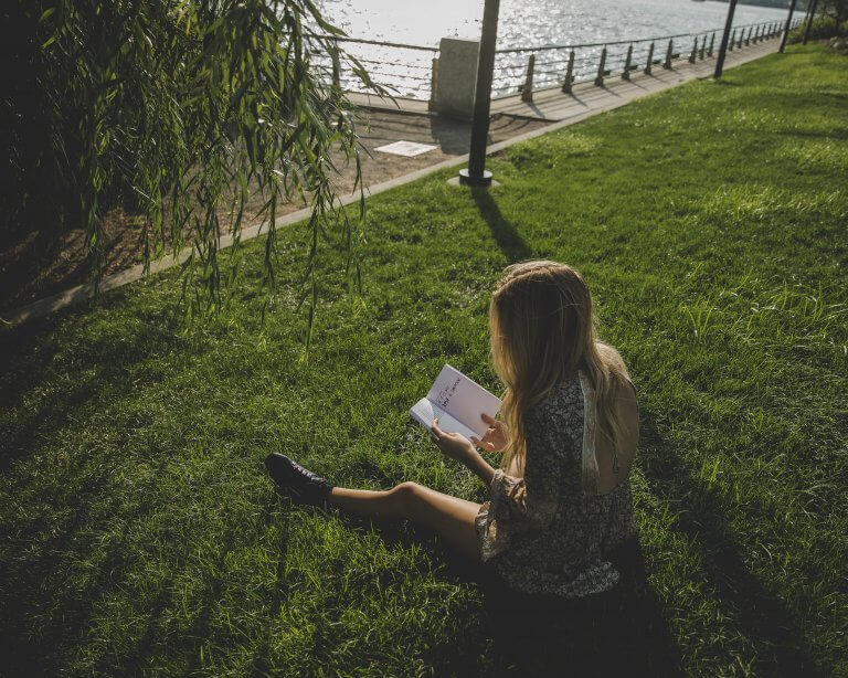 A woman sitting on the grass making time for herself to read a book