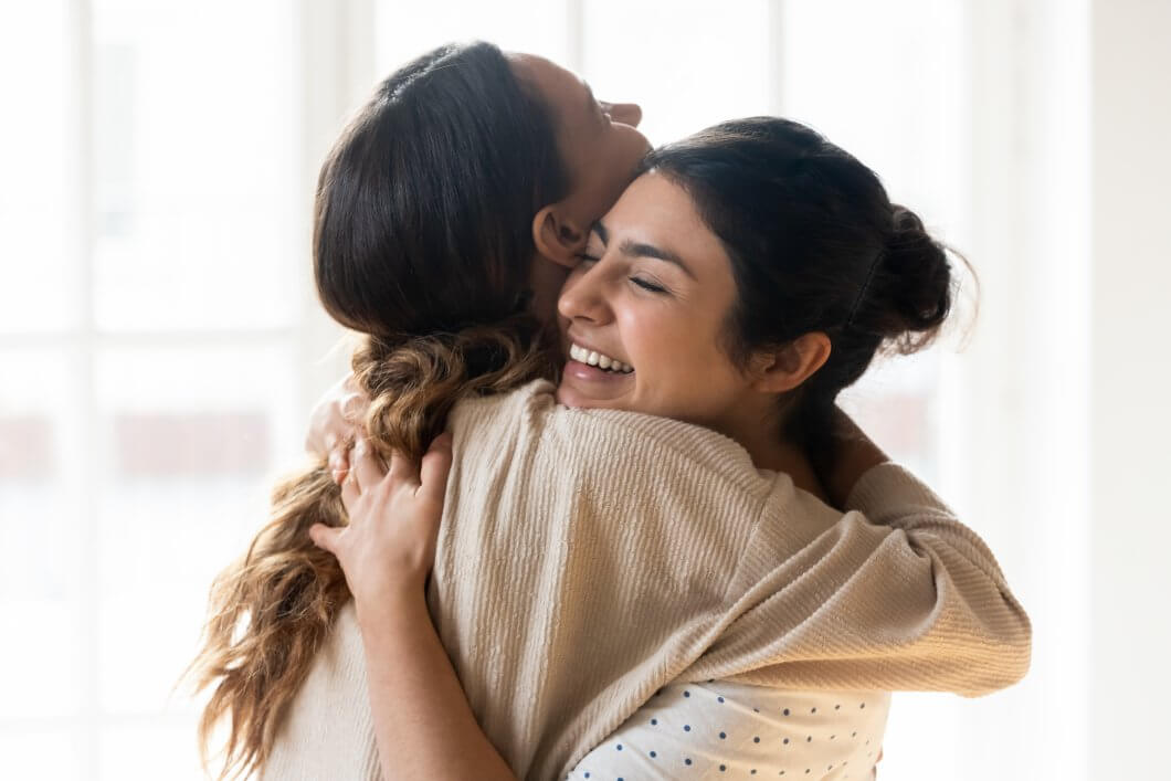 Two women celebrating the process of forgiveness with a hug