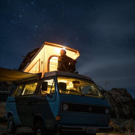 A man managing his stress by relaxing on top of wagon gazing at the stars