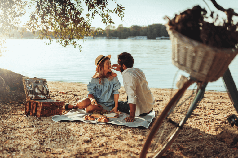 A couple by the water at a local park having an enjoyable picnic and cheap date