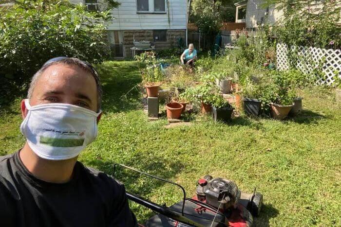 Brian Schwartz, foreground, mows the lawn of Lois Reichert, background, in West Orange, N.J.