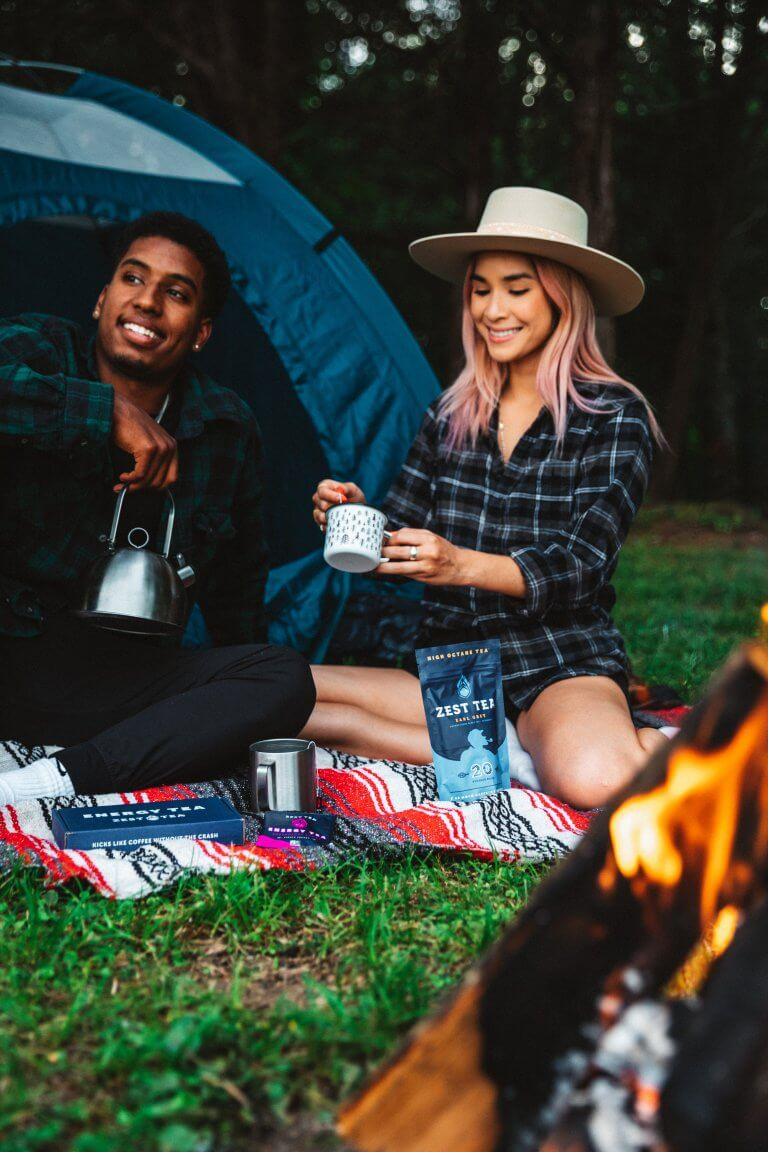 A couple sitting outside of a tent enjoying a cheap date