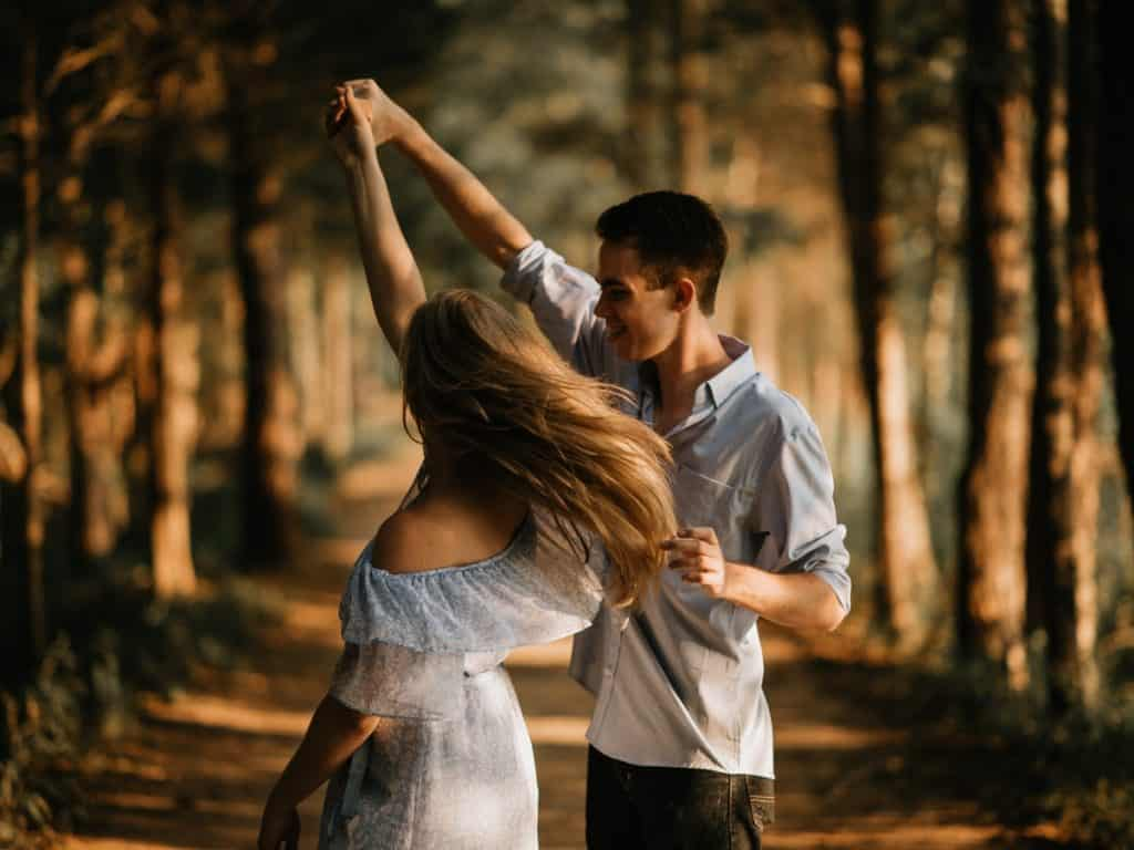 A young couple in love, dancing in the woods.