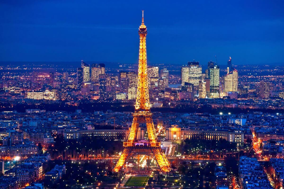 A lit up Eiffel Tower at night, overlooking downtown Paris