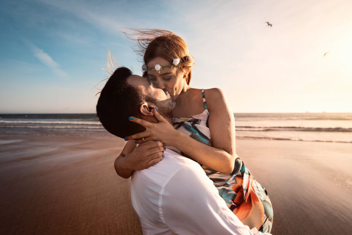 A kissing couple at the beach kissing after taking the love quiz