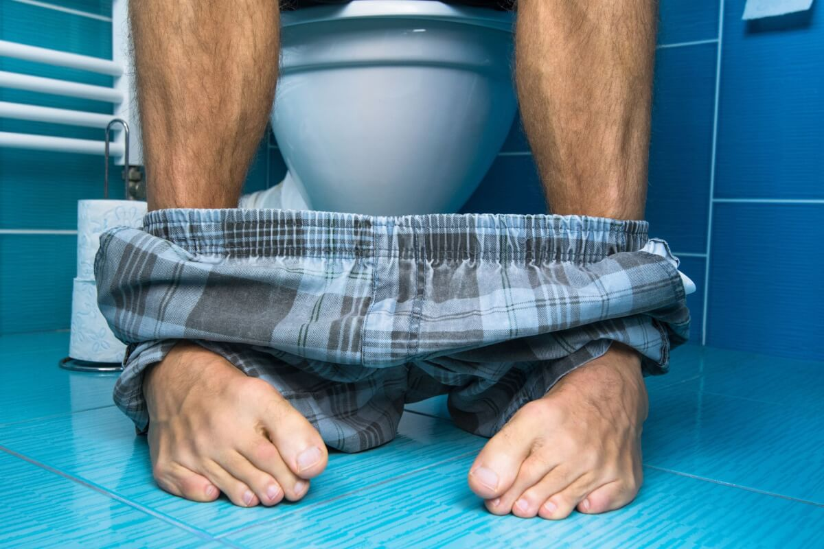 A man in his pajamas sitting on the toilet seat taking a poop