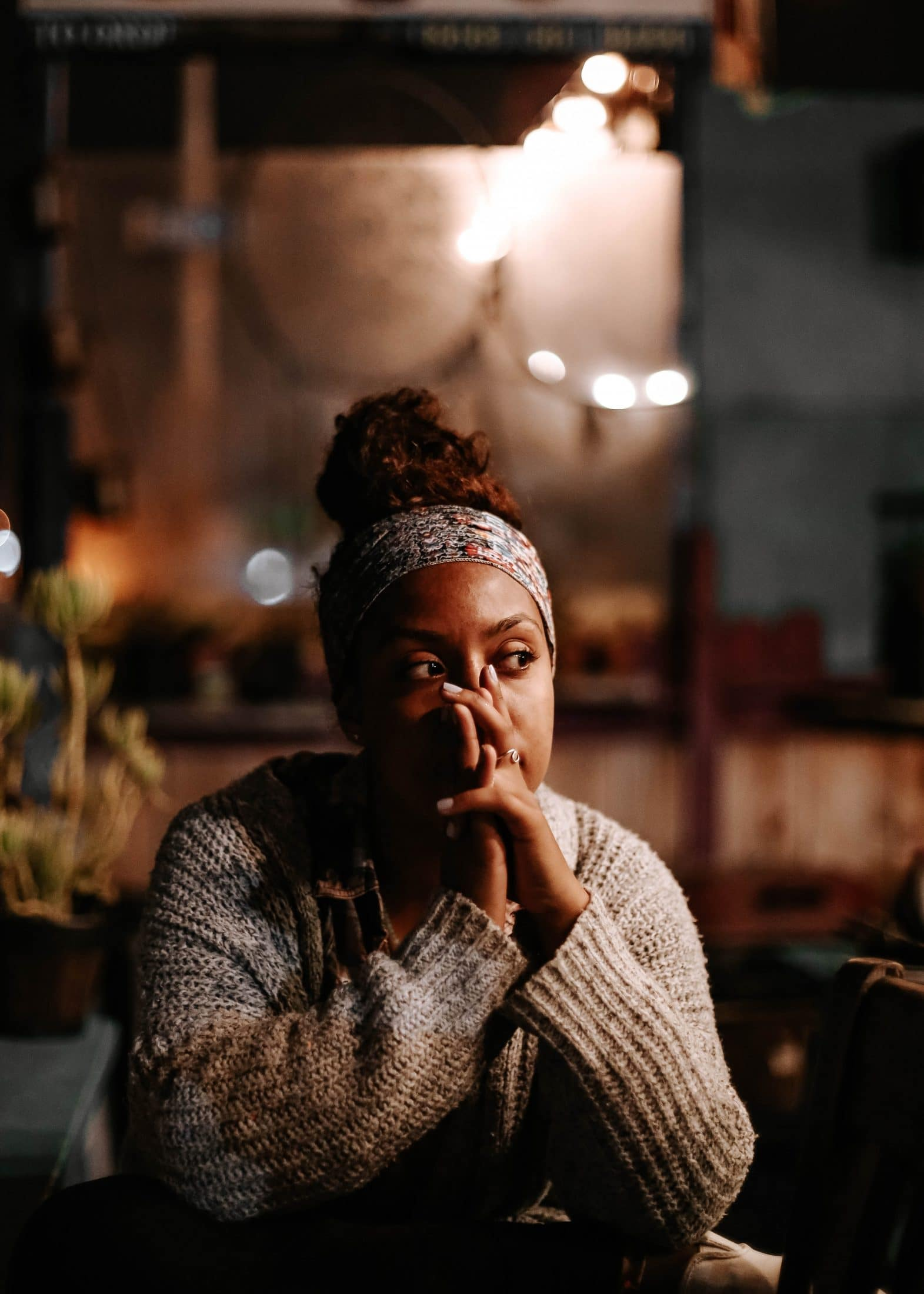 An overthinking black woman who looks stressed and anxious