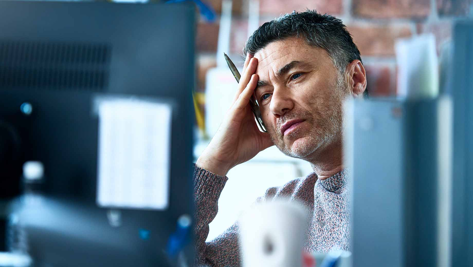 A man in front of his computer looking stressed and burnt out at work