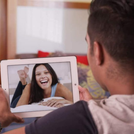 A couple in a long-distance relationship chatting on their iPads
