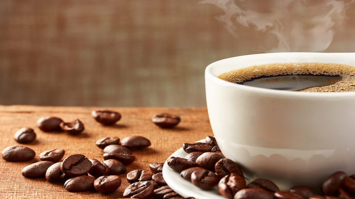 A healthy cup of warm coffee and coffee beans