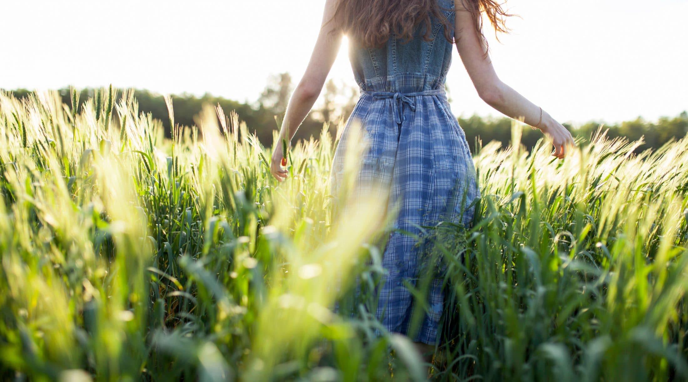 A woman with energy strolling in a field, enjoying fresh air