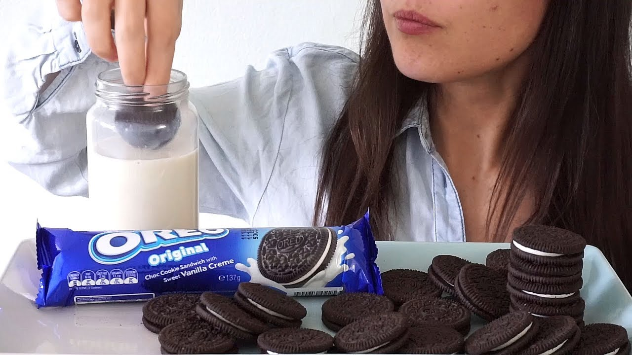 A woman dipping her Oreo cookie in milk