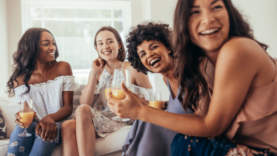 smiling is contagious as a group of women are smiling and laughing over drinks