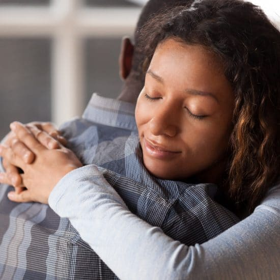 An African-American couple hugging, apologizing