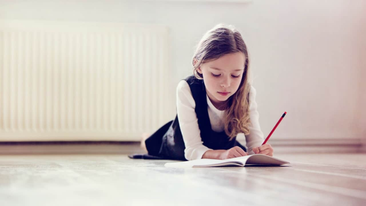 A left-handed autistic girl drawing in a journal
