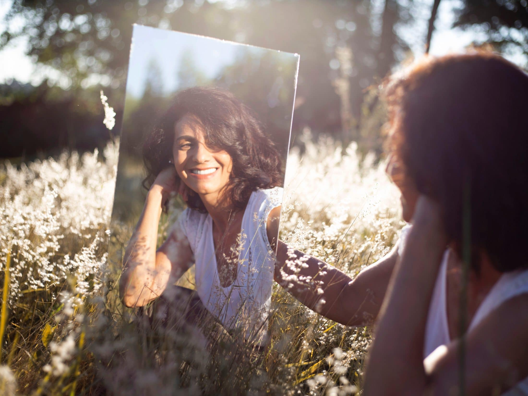 A happy woman outdoors, smiling in a mirror